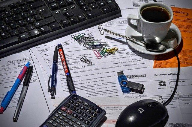bureau avec calculettes, feuilles de comptes, trombones etc